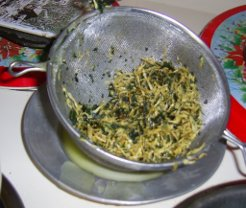 strained herbs in sieve